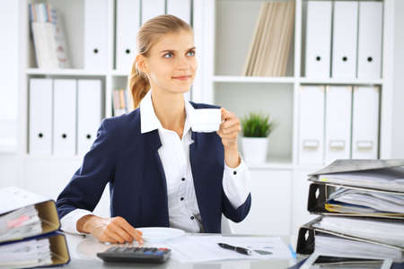 Happy business woman or female accountant having some minutes for coffee and pleasure at working place Stock Photo