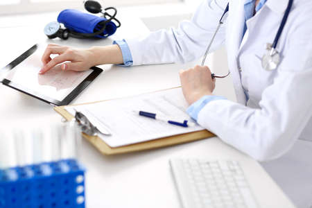 Woman doctor using tablet computer while sitting at the desk in hospital closeup. Cardiologist checks heart diagrams with tablet pc. Healthcare, insurance and smart technology in medicine concept Stock Photo