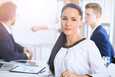 Business People at meeting in office. Focus at beautiful cheerful smiling woman. Conference, corporate training or brainstorming of people group. Success and  negotiation concept Stock Photo