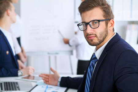 Business people at meeting in office. Focus at cheerful smiling bearded man wearing glasses. Conference, corporate training or brainstorming of people group. Success and negotiation concept Stock Photo