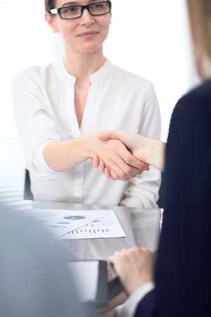 Close Up of unknown business people shaking hands while finishing up a meeting. Handshaking, agreement or success concept in people communication