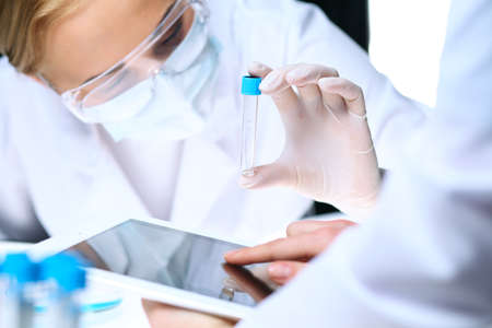 Closeup of scientific research team with clear solution in laboratory. Blonde female chemist holds test tube of glass while her colleague checks results with tablet pc. Blood test, medicine or chemical manufacturing concept Stock Photo