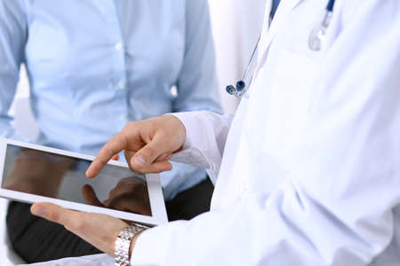 Male doctor using touchpad or tablet computer while consulting female patient in hospital. Medicine and healthcare concept