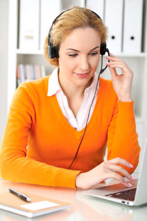 Young beautiful business woman in headset or call operator communicates by laptop computer. Orange sweater is uniform of a girl