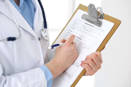 Female doctor filling up medical form on clipboard closeup.  Physician finishing up examining his patient in hospital and ready to give a prescription to help. Healthcare, insurance and medicine concept