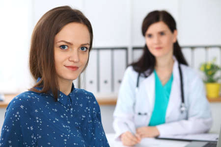 Doctor and patient having a talk while sitting at the desk. Focus on young beautiful woman looking at camera