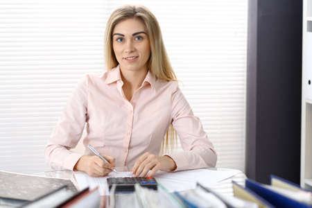 Retrato de mujer contable o inspector financiero haciendo informe, calculando o comprobando el saldo. Copie el área del espacio