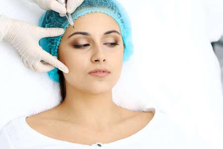 Professional beautician doing eyebrow tattoo at woman face. Permanent brow makeup in beauty salon, closeup.  Cosmetology treatment