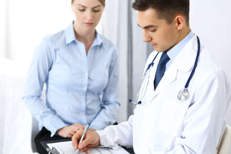 Male doctor holding application form while consulting female patient in hospital office. Perfect service in medicine and healthcare concept Stock Photo