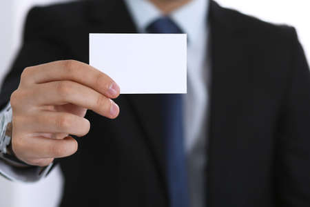 Businessmans hand holding business card with empty space 写真素材