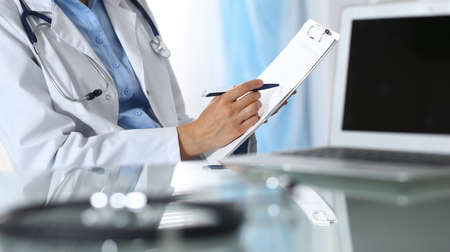 Female doctor filling up medical form on clipboard, closeup. Reflecting glass table is a physician working place. Healthcare, insurance and medicine concept Banque d'images
