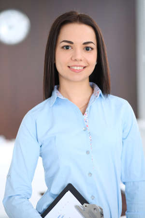 Young brunette business woman looks like a student girl working in office. Hispanic or latin american girl standing straight Stok Fotoğraf - 101988160
