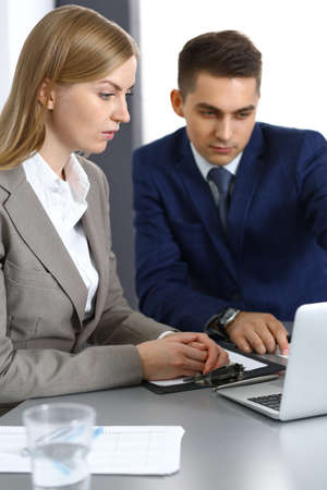 Business people using laptop pc while discussing project in office