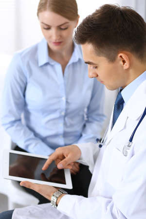 Male doctor using touchpad or tablet pc while consulting female patient in hospital office. Medicine and healthcare concept Stock Photo