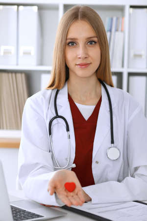 Female doctor with stethoscope holding heart in her arms. Healthcare and cardiology concept  in medicine Stock Photo