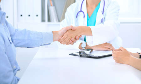 Doctor and family couple of patient are discussing something, just hands at the table. Medicine concept