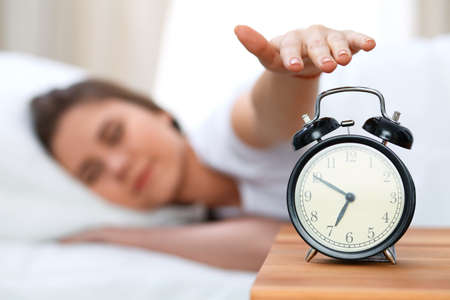 Sleepy young woman stretching hand to ringing alarm willing turn it off. Early wake up, not getting enough sleep concept
