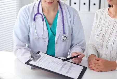 Arts en patiënt, close-up van handen. Arts die over de resultaten van medisch onderzoek spreekt. Geneeskunde, gezondheidszorg en helpen concept Stockfoto