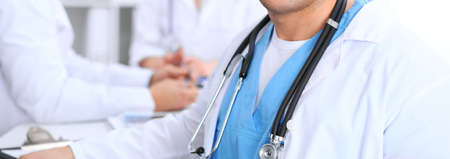 Unknown male doctor is sitting at the table and working in the hospital office. Closeup of stethoscope