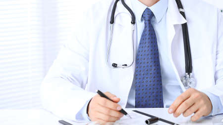Unknown male doctor is sitting at the table and working in the hospital office. Closeup of stethoscope. Stock Photo