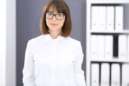 Young brunette business woman looks like a student girl working in office. Caucasian  girl standing straight Foto de archivo