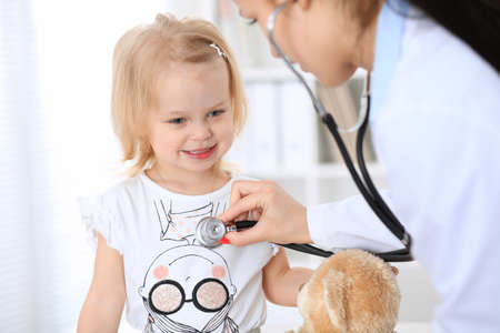 Doctor and patient baby in hospital. Little girl is being examined by pediatrician with stethoscope. Health care, insurance and help concept Reklamní fotografie