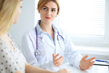 Doctor and patient discussing something while sitting at the desk at hospital. Medicine and health care concept