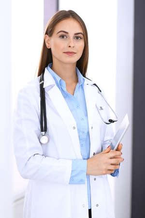 Arztfrau mit Tablet-Computer, während sie gerade in der Nähe des Fensters im Krankenhaus steht. Glücklicher Arzt bei der Arbeit. Medizin- und Gesundheitskonzept