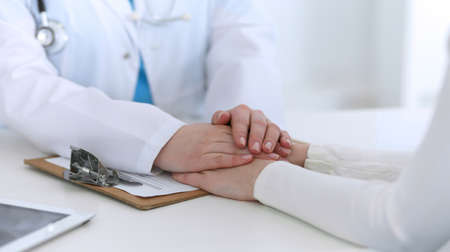 Medicine doctor hand reassuring her female patient closeup. Medicine, comforting and trusting concept in health care.
