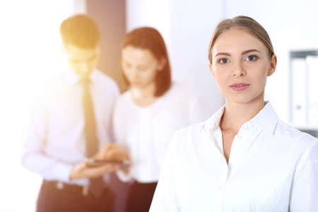 Beautiful blonde businesswoman standing straight in a brightly lit office at the background of colleagues or partners. Business concept.