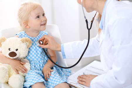 Doctor examining a little blonde girl with stethoscope.Medicine and healthcare concept