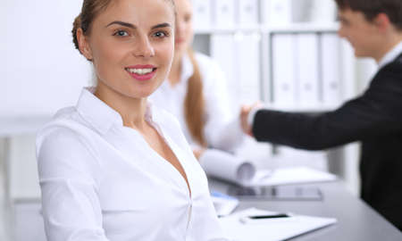 Group of business people at meeting on the background of office. Focus at a beautiful brunette woman