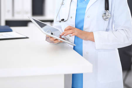 Close-up of female physician using digital tablet  while standing near reception desk at clinic or emergency hospital. Unknown doctor woman at work. Medicine and healthcare concept 免版税图像