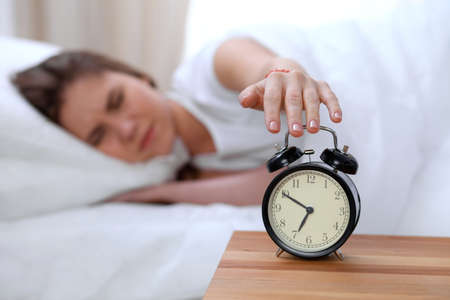 Alarm clock opposite of sleepy young woman stretching hand to ringing alarm willing turn it off. Early wake up, not getting enough sleep concept