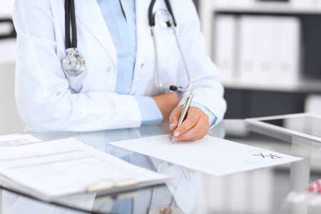Doctor woman filling up prescription form while sitting at the desk in hospital close-up.  Physician at work and ready to give an advice to help patient. Healthcare, insurance and excellent service in medicine concept Stockfoto