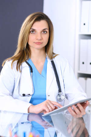 Woman doctor at work in hospital office. Portrait of female physician. Medicine and health care concept