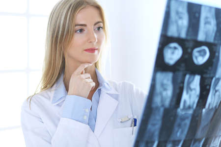 Doctor woman osteopathist examining x-ray picture while standing near window in clinic or hospital. Medicine and healthcare concept