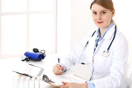Mujer médico que usa el portapapeles con formulario de registro médico mientras está sentado cerca de la ventana en la clínica o el hospital. Concepto de medicina y salud. Médico en el trabajo