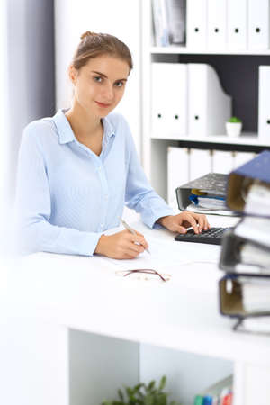 Woman bookkeeper or financial inspector calculating or checking balance, making report. Internal Revenue Service at work with financial document. Tax and audit concept