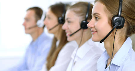 Call center operator in headset while consulting client. Telemarketing or phone sales