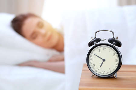 Alarm clock opposite of beautiful young woman sleeping while lying in bed comfortably and blissfully. Happy waking up early for a job Banco de Imagens