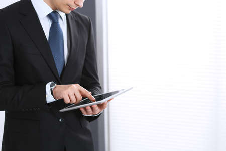 Businessman using digital tablet while standing near window in office, close-up. Copy space area Фото со стока