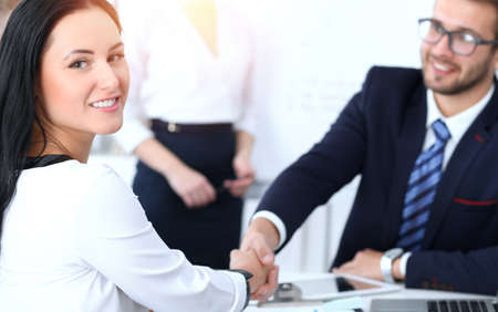 Business handshake at meeting or negotiation in the office. Two businesspeople partners are satisfied because signing contract or financial papers