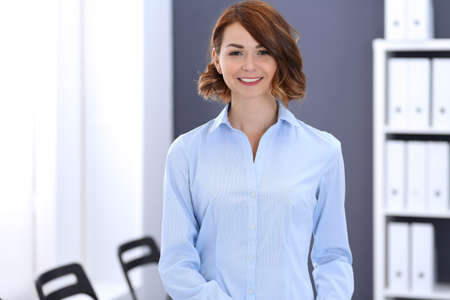 Young brunette business woman looks like a student girl working in office. Caucasian  girl standing straight 版權商用圖片