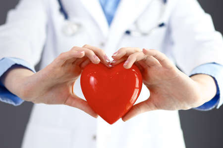 Female doctor with stethoscope holding heart in her arms. Healthcare and cardiology concept  in medicine Stok Fotoğraf