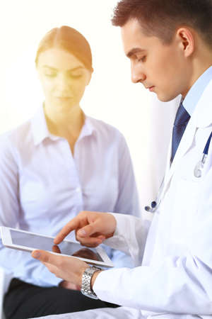 Male doctor using touchpad or tablet pc while consulting female patient in hospita. Medicine and healthcare concept