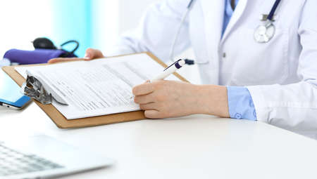 Female doctor using medical form on clipboard closeup.  Physicianat work in hospital or clinic. Healthcare, insurance and medicine concept Stockfoto