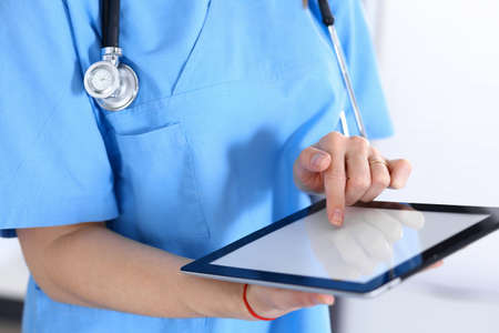 Woman doctor using tablet computer while standing straight in hospital office, closeup. Healthcare, insurance and medicine concept