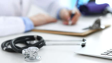 Closeup of stethoscope. Female doctor fills up medical form while sitting at the desk in hospital. Healthcare, workplace and cardiology in medicine concept.