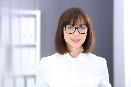 Young brunette business woman looks like a student girl working in office. Caucasian  girl standing straight Stockfoto